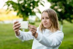Colegiala de la niña El Blonde está llevando a cabo las manos con el teléfono Tome a fotos su smartphone Verano en naturaleza víd Fotos de archivo libres de regalías