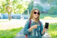 Colegiala de la niña En verano en parque en aire fresco Lleva a cabo las manos del teléfono con un gesto de la mano y del punto a Imágenes de archivo libres de regalías