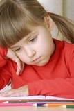 Colegiala de la tristeza que piensa y que tachona. Imagen de archivo libre de regalías