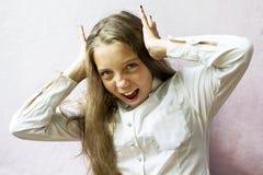 Colegiala de pelo rubio linda de la muchacha en un fondo ligero Educación Emociones y sensaciones Fotografía de archivo