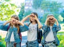 Colegiala de tres muchachas Él ` s en naturaleza El gesto muestra su corazón con sus manos Vestido en ropa de los vaqueros r Fotos de archivo