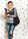 Colegiala del adolescente con el libro de textos Foto de archivo libre de regalías
