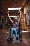 Colegiala discapacitada en la silla de ruedas en pasillo en la escuela Fotografía de archivo
