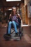 Colegiala discapacitada en la silla de ruedas en pasillo en la escuela Fotografía de archivo libre de regalías