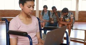 Colegiala discapacitada que usa la tableta digital con los compañeros de clase en fondo almacen de video