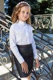 Colegiala dulce hermosa de la muchacha en uniforme escolar afuera en un día soleado con el pelo rizado y una guirnalda de rosas d Imágenes de archivo libres de regalías
