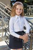 Colegiala dulce hermosa de la muchacha en uniforme escolar afuera en un día soleado con el pelo rizado y una guirnalda de rosas d Fotografía de archivo