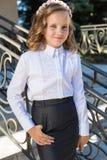 Colegiala dulce hermosa de la muchacha en uniforme escolar afuera en un día soleado con el pelo rizado y una guirnalda de rosas d Imagen de archivo