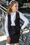 Colegiala dulce hermosa de la muchacha en uniforme escolar afuera en un día soleado con el pelo rizado y una guirnalda de rosas d Imagen de archivo libre de regalías