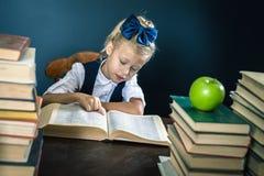 Colegiala elegante que lee un libro en la biblioteca Fotos de archivo