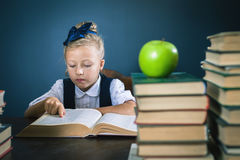 Colegiala elegante que lee un libro en la biblioteca Imagenes de archivo