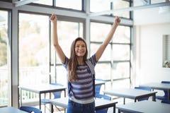 Colegiala emocionada que se coloca con los brazos para arriba en sala de clase Fotos de archivo libres de regalías
