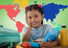 Colegiala en el escritorio delante del mapa del mundo colorido Imagen de archivo libre de regalías