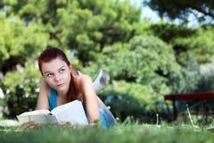 Colegiala en el parque con el libro Imágenes de archivo libres de regalías