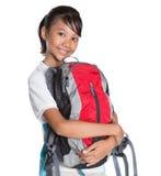 Colegiala en el uniforme escolar y la mochila XII Imagenes de archivo