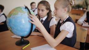 Colegiala en la clase de la geografía que estudia los países y los continentes con el globo metrajes