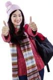 Colegiala en la ropa del invierno que da los pulgares para arriba Imágenes de archivo libres de regalías