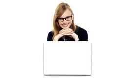 Colegiala encantadora que se sienta con su computadora portátil abierta Foto de archivo libre de regalías