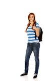 Colegiala feliz con la mochila y el pulgar para arriba Imagenes de archivo