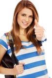 Colegiala feliz con la mochila y el pulgar para arriba Imagen de archivo