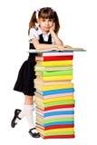 Colegiala feliz con una pila de libros pesados Foto de archivo libre de regalías