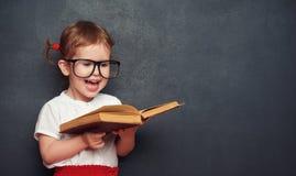 Colegiala feliz divertida de la muchacha con el libro de la pizarra imagenes de archivo
