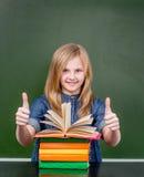 Colegiala feliz en la sala de clase que muestra el pulgar para arriba Fotos de archivo libres de regalías