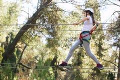 Colegiala feliz que disfruta de actividad en un parque de la aventura que sube Imágenes de archivo libres de regalías