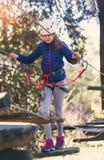 Colegiala feliz que disfruta de actividad en un parque de la aventura que sube Foto de archivo libre de regalías
