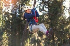 Colegiala feliz que disfruta de actividad en un parque de la aventura que sube fotos de archivo