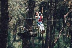 Colegiala feliz que disfruta de actividad en un parque de la aventura que sube Imagenes de archivo