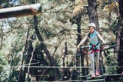 Colegiala feliz que disfruta de actividad en un parque de la aventura que sube Imagen de archivo libre de regalías