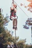 Colegiala feliz que disfruta de actividad en un parque de la aventura que sube Foto de archivo