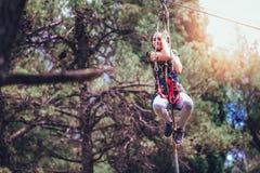 Colegiala feliz que disfruta de actividad en un parque de la aventura que sube Imagen de archivo