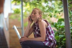 Colegiala feliz que habla en el teléfono móvil Foto de archivo