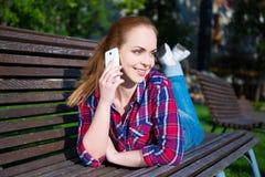 Colegiala feliz que habla en el teléfono móvil en parque Foto de archivo libre de regalías