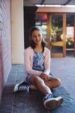 Colegiala feliz que se sienta al lado de la pared de ladrillo en campus de la escuela Imágenes de archivo libres de regalías