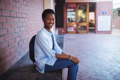 Colegiala feliz que se sienta con el bolso de escuela en campus de la escuela Imagen de archivo