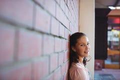 Colegiala feliz que se sienta contra la pared de ladrillo en campus de la escuela Imagen de archivo libre de regalías