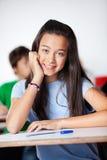 Colegiala feliz que se sienta en el escritorio en sala de clase Fotografía de archivo libre de regalías