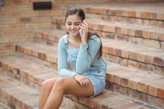 Colegiala feliz que se sienta en escalera y el teléfono móvil que habla Imagen de archivo