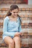 Colegiala feliz que usa el teléfono móvil en escalera Fotos de archivo