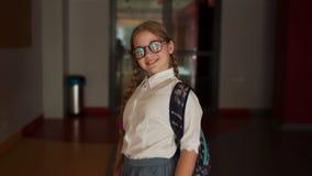 Colegiala hermosa del adolescente en el vestíbulo de la escuela La muchacha lleva los vidrios y dos coletas, ella tiene una taleg almacen de video