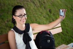 Colegiala hermosa que hace la foto del selfie en smartphone en parque Imagen de archivo