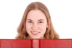 Colegiala hermosa que mira furtivamente de detrás su libro rojo Fotos de archivo