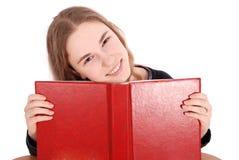 Colegiala hermosa que mira furtivamente de detrás su libro rojo Imágenes de archivo libres de regalías
