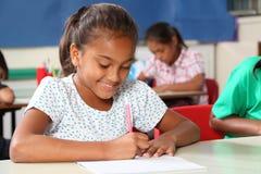 Colegiala joven en la escritura ocupada de la sala de clase en el escritorio Fotografía de archivo