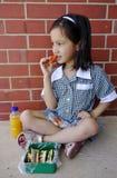 Colegiala joven que come su almuerzo. Fotografía de archivo libre de regalías