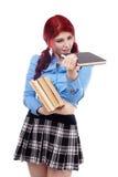 Colegiala joven que hojea a través de una pila de libros Foto de archivo libre de regalías