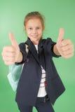 Colegiala joven sonriente que muestra los pulgares para arriba Foto de archivo